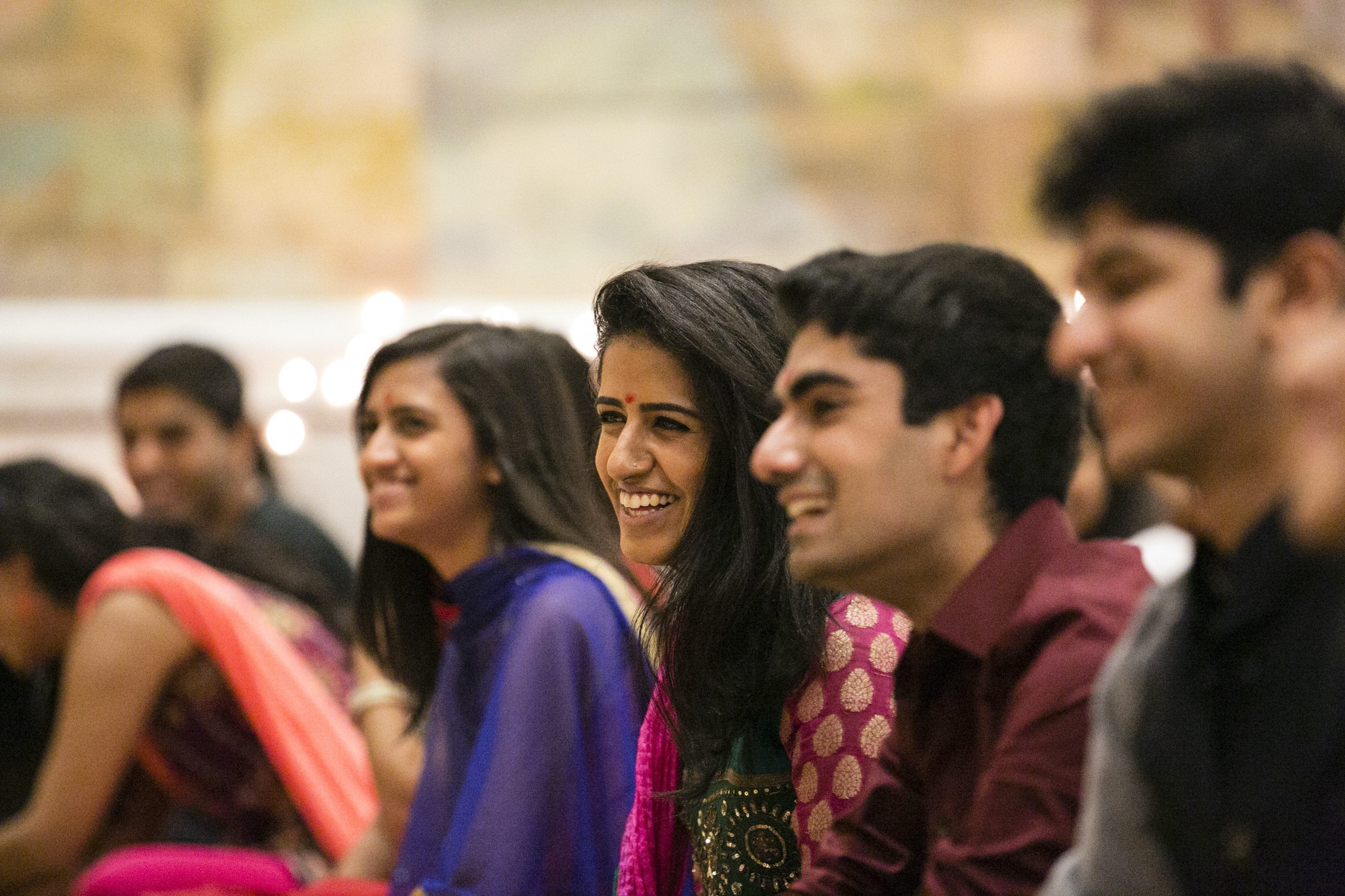 Six Hindu students face an altar off camera and smile