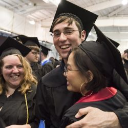 Three graduates in caps and gowns smile and hug