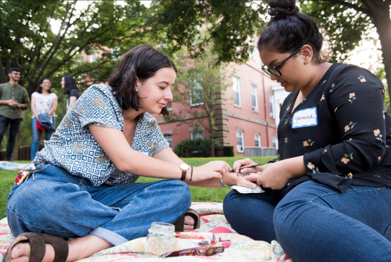 Two people are sitting; the person on the right is drawing henna on the hand of the other person, and they are both looking at it together. Photo credit: Tufts University Photography