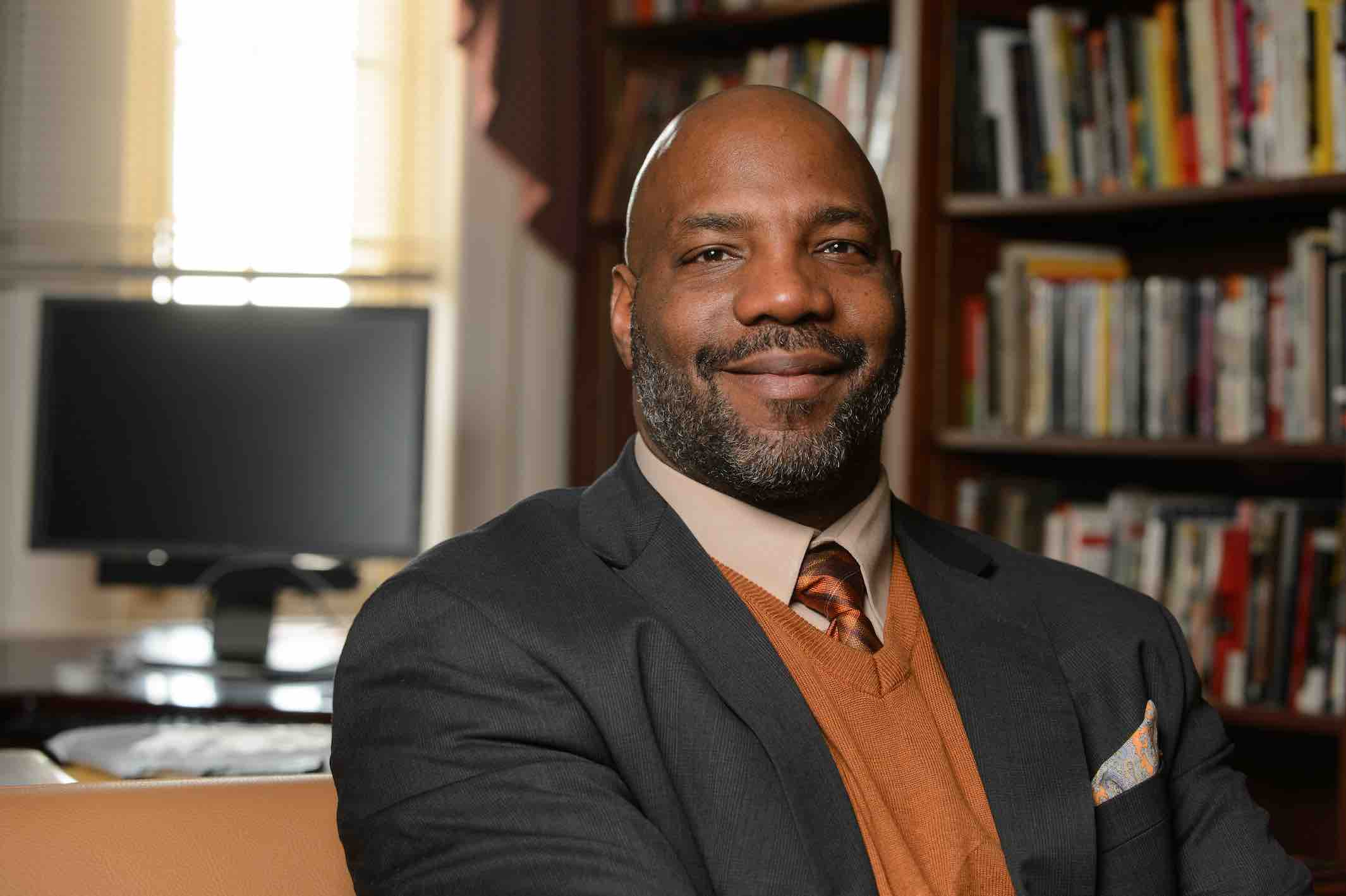 Jelani Cobb, a Black man in a suit jacket, smiles at the camera; in the foreground: bookshelves and a computer