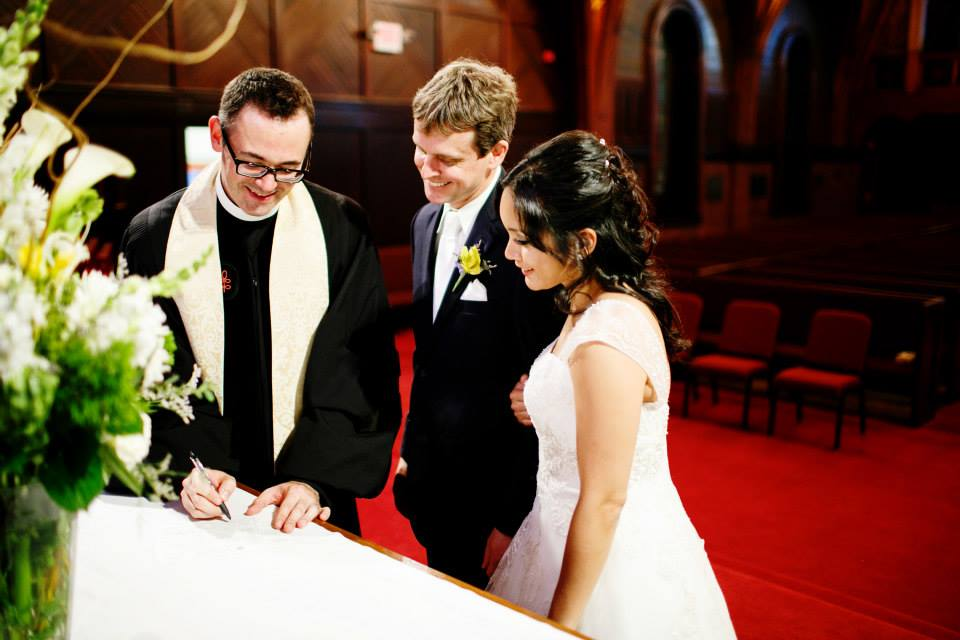 Tufts Professor Ethan Danahy and Kristina Danahy sign their wedding license in Goddard Chapel with Tufts University Chaplain The Reverend Greg McGonigle.